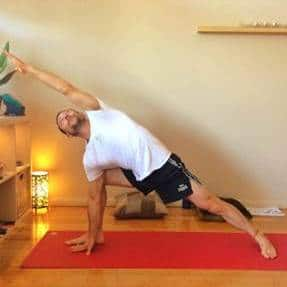 Man in tshirt and shorts doing side angle yoga pose